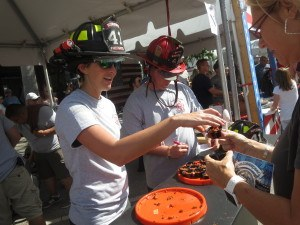 firefighter-jamie-wolfe-passes-out-chili-alongside-lt-sean-thorton-from-the-nokomis-fire-department-at-their-smoke-eaters-booth